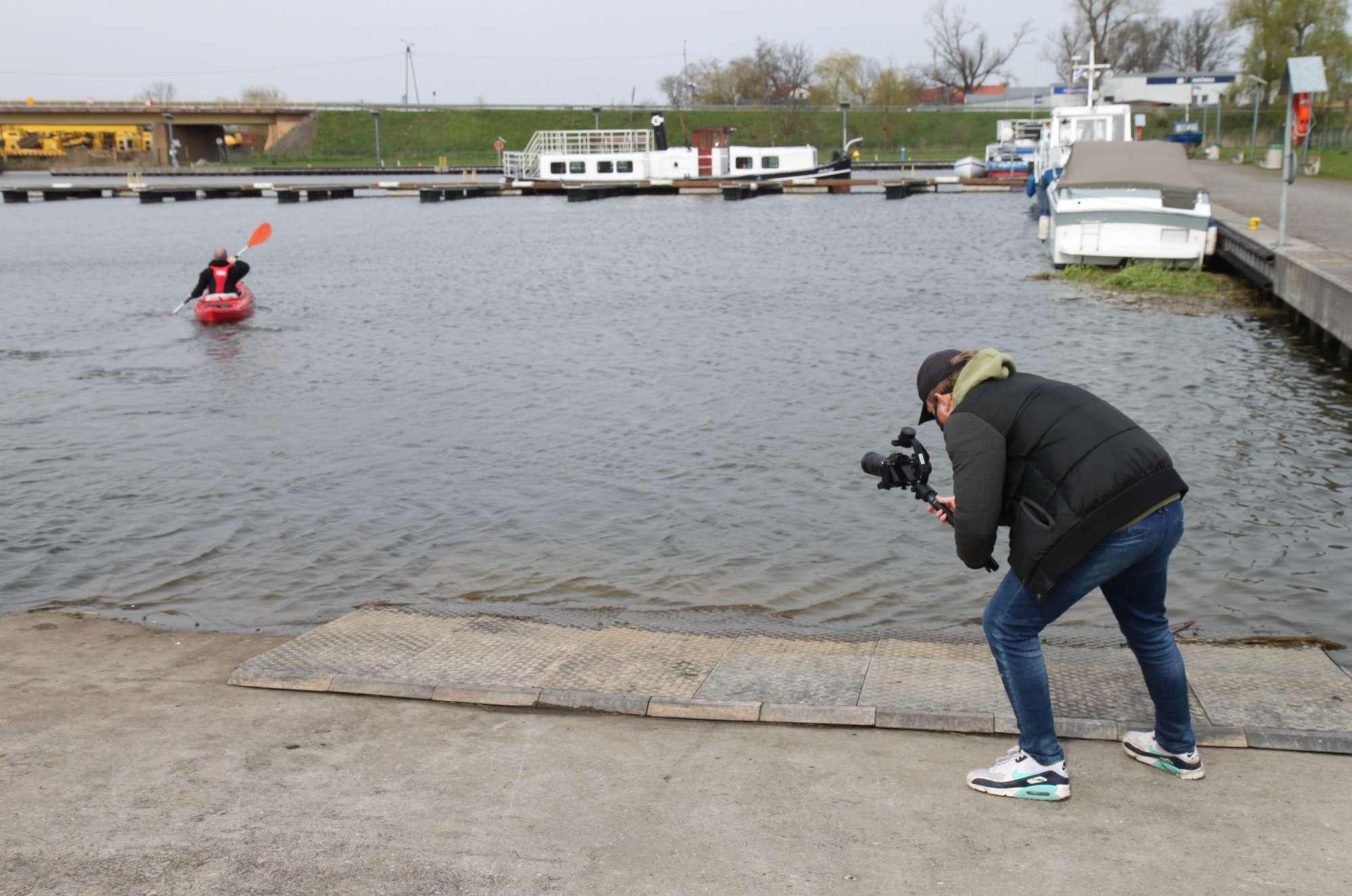 Kręcenie filmu - kamerzysta nagrywa mężczyznę płynącego kajakiem