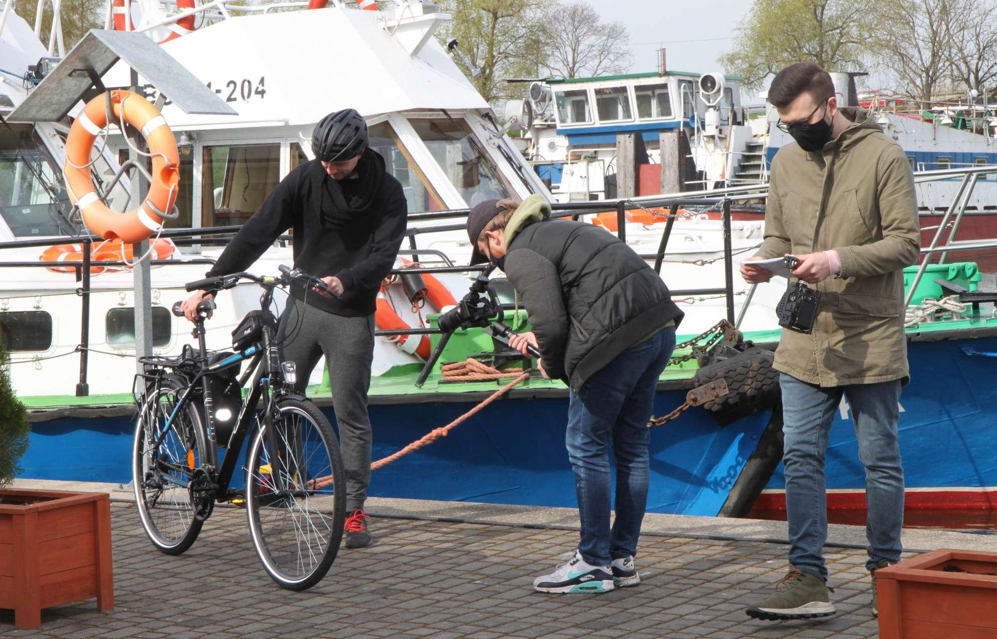 Kręcenie filmu - scena pokazuje mężczyznę stojącego obok roweru na tle statku